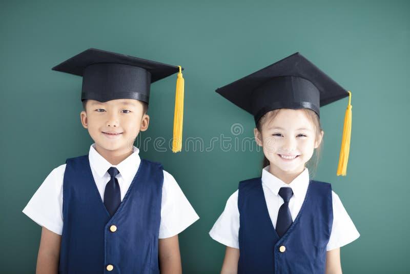 el muchacho y la muchacha en casquillo de la graduación se colocan antes de pizarra imagenes de archivo