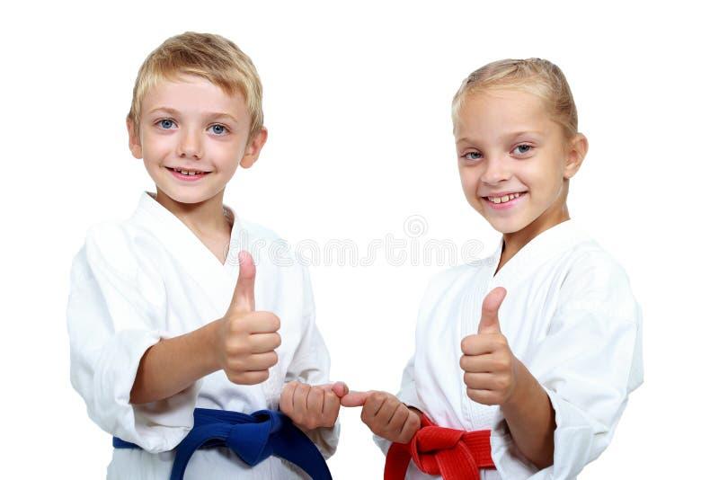 El muchacho y la muchacha en karategi están mostrando el pulgar estupendo imagen de archivo libre de regalías
