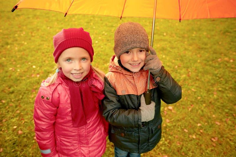 El muchacho y la muchacha felices con el paraguas en otoño parquean imagenes de archivo