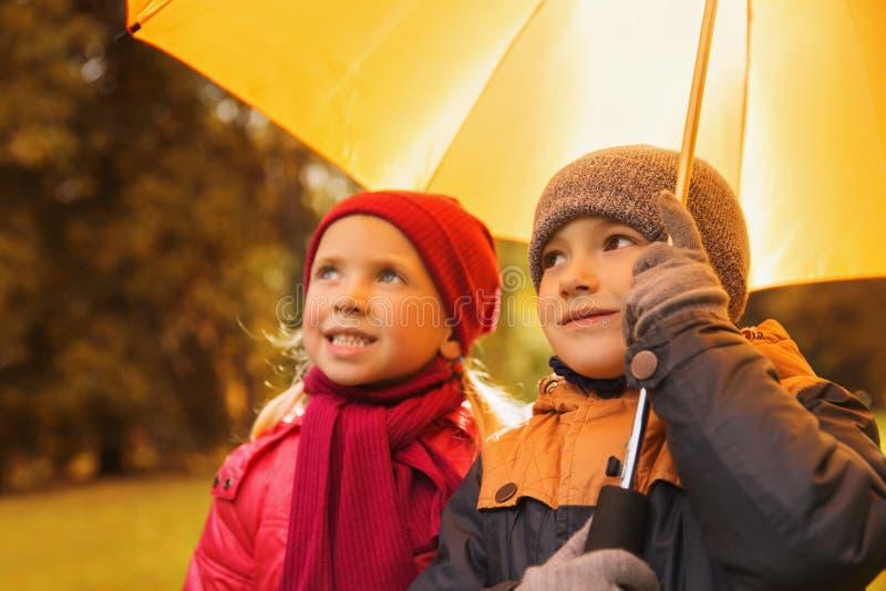 El muchacho y la muchacha felices con el paraguas en otoño parquean foto de archivo