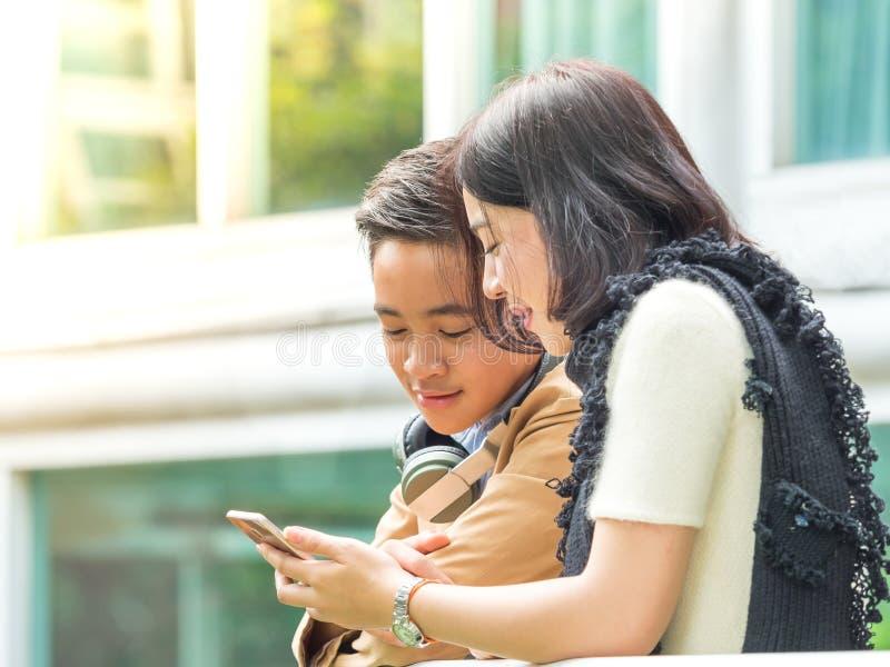 El muchacho y la muchacha jovenes juegan a juegos en los teléfonos móviles fotografía de archivo libre de regalías
