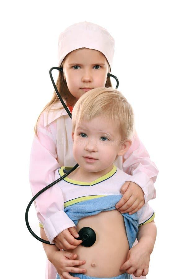El muchacho y la muchacha juegan al doctor imagen de archivo