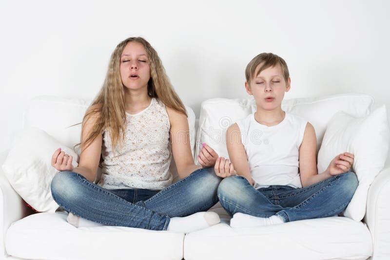 El muchacho y la muchacha meditan fotos de archivo libres de regalías