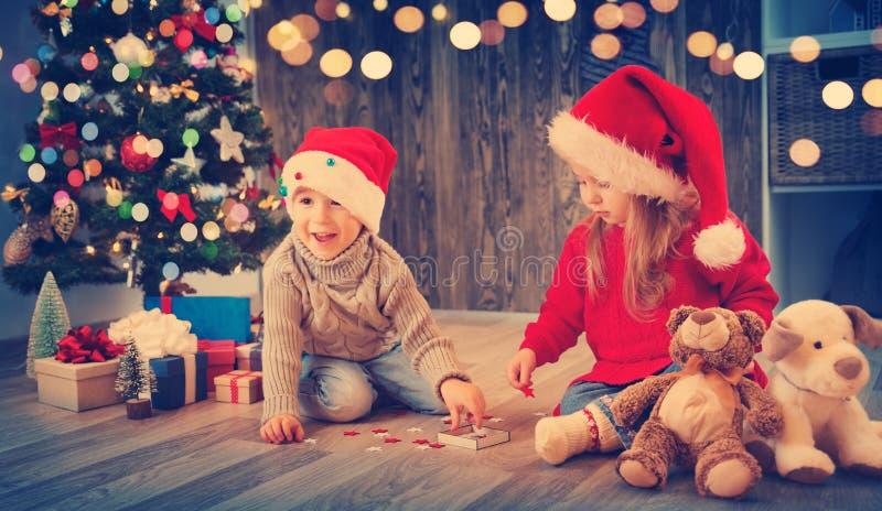 El muchacho y la muchacha que mienten en el piso con los presentes acercan al árbol de navidad fotos de archivo libres de regalías