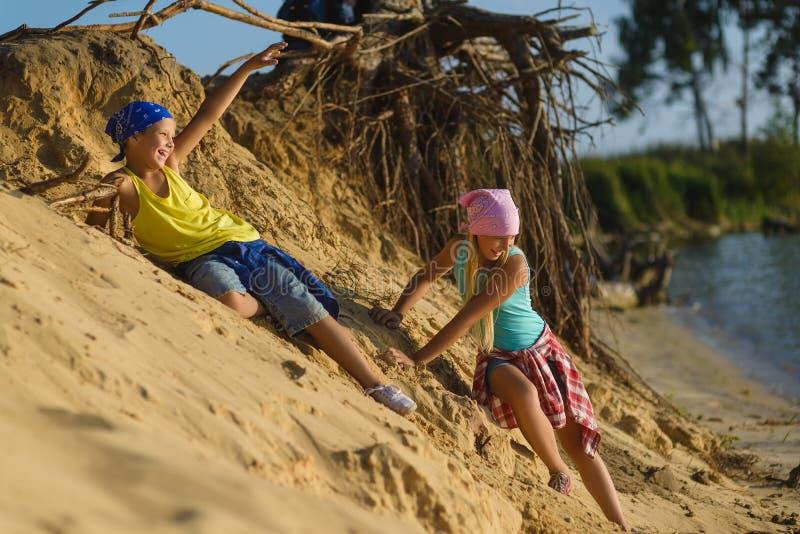 El muchacho y la muchacha van abajo de la arena a la playa Aventura, viaje, concepto del turismo foto de archivo libre de regalías