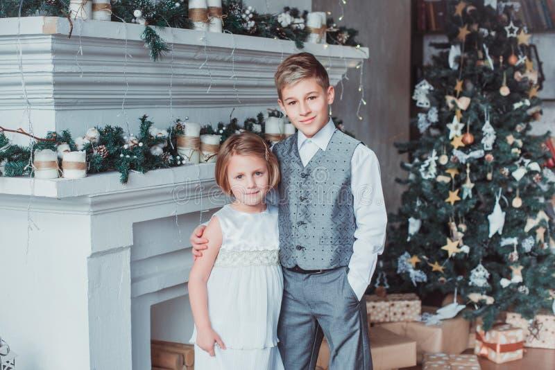 El muchacho y la muchacha vistieron elegante la colocación en un cuarto brillante por la chimenea Árbol de navidad en el fondo Co fotos de archivo