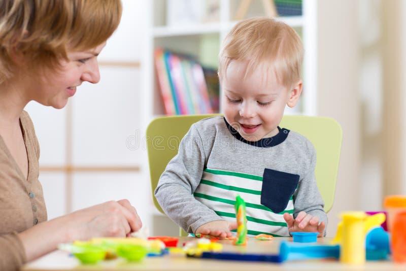 El muchacho y la mujer del niño del niño que juegan la arcilla colorida juegan en el cuarto de niños o la guardería fotografía de archivo libre de regalías