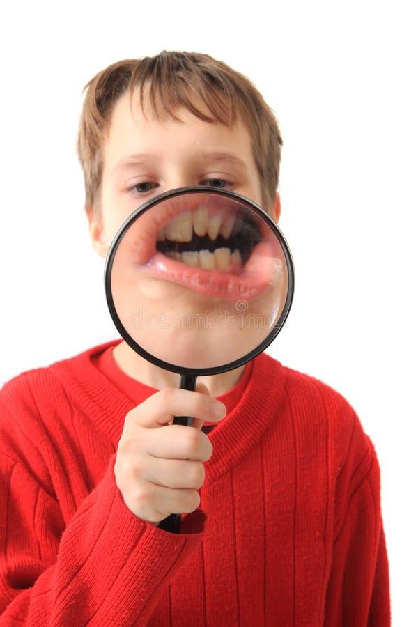 El muchacho y magnifica el vidrio fotografía de archivo