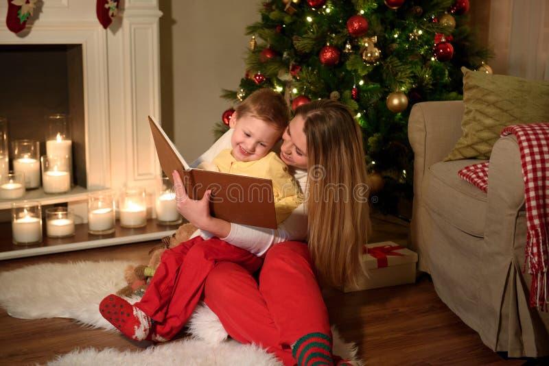 El muchacho y su mamá están leyendo un libro que ríen juntos fotos de archivo libres de regalías