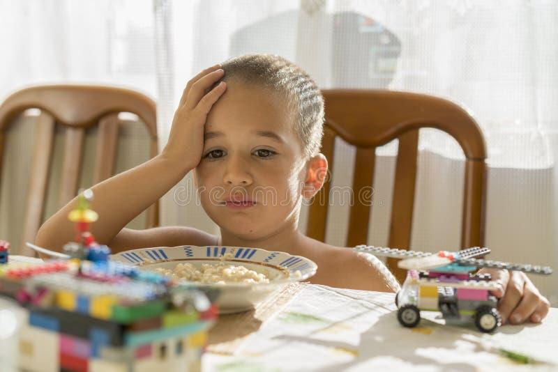 El muchacho 4years come las gachas de avena Children& x27; tabla de s El concepto del child& x27; independencia de s consumición  fotos de archivo libres de regalías