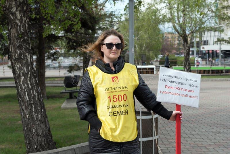 el Mujer-activista se coloca con un cartel en sus manos y una inscripción en la ropa: 1500 familias engañadas fotografía de archivo