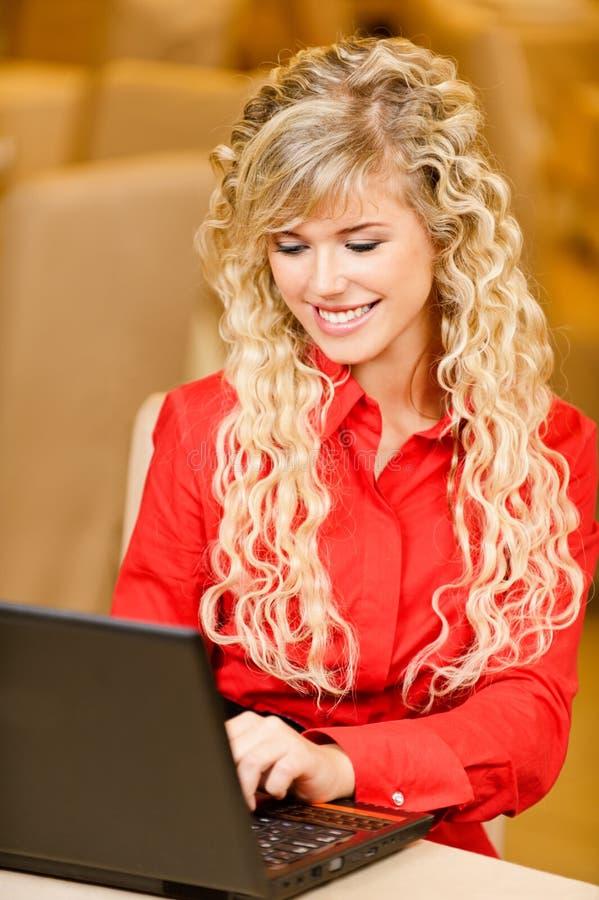 el Mujer-estudiante trabaja en la computadora portátil negra fotografía de archivo libre de regalías