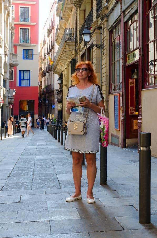 el Mujer-turista con el mapa en sus manos está en la calle estrecha en el cuarto gótico famoso, Barcelona, España fotos de archivo libres de regalías