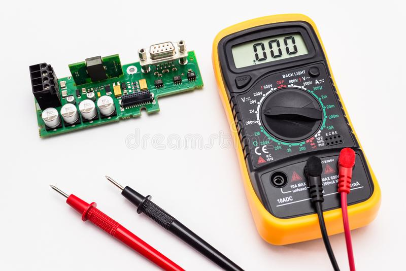 El multímetro eléctrico con rojo y el negro sondan, exhibición que indica cero, con la placa de circuito impresa Aislado en un fo fotos de archivo