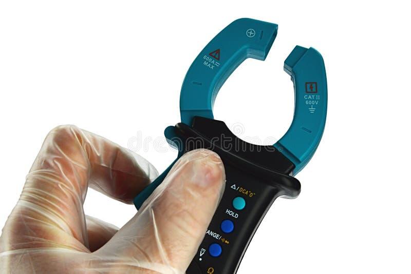 El multímetro eléctrico de la abrazadera moderna se sostuvo en mano izquierda en el guante transparente del látex, fondo blanco imagen de archivo libre de regalías