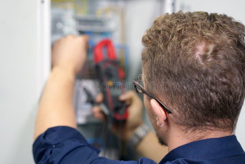 El multímetro está en manos del electricista en el fondo del electrica fotos de archivo