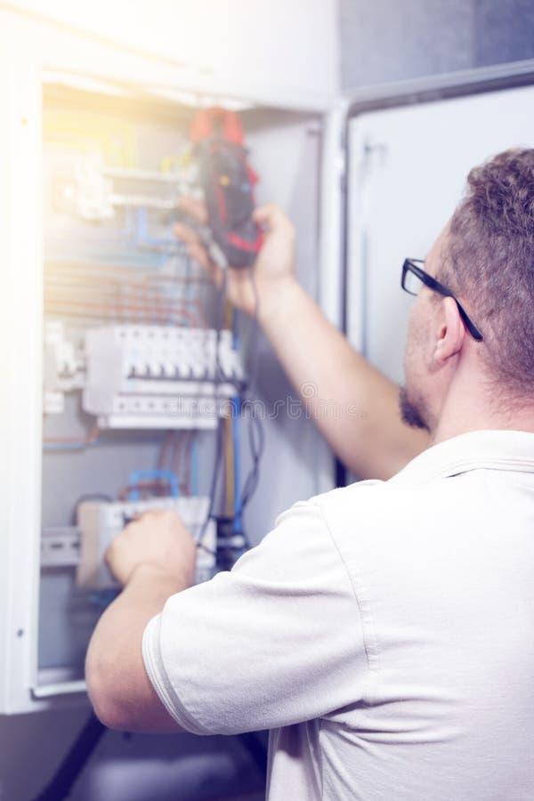 El multímetro está en manos del electricista en fondo del gabinete eléctrico de la automatización Ajuste del circuito de control  fotografía de archivo