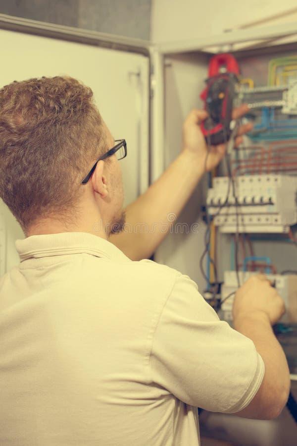 El multímetro está en manos del electricista en fondo del gabinete eléctrico de la automatización Ajuste del circuito de control  imagen de archivo