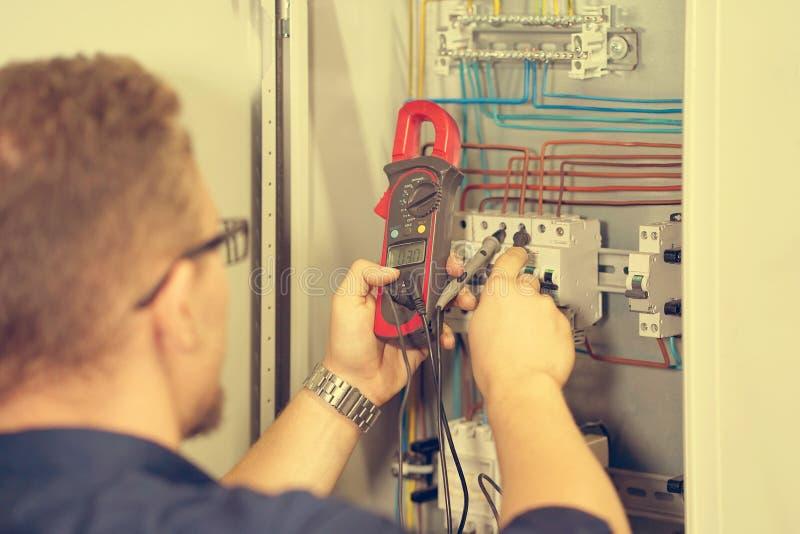 El multímetro está en manos del electricista en fondo del gabinete eléctrico de la automatización Ajuste del circuito de control  fotos de archivo libres de regalías