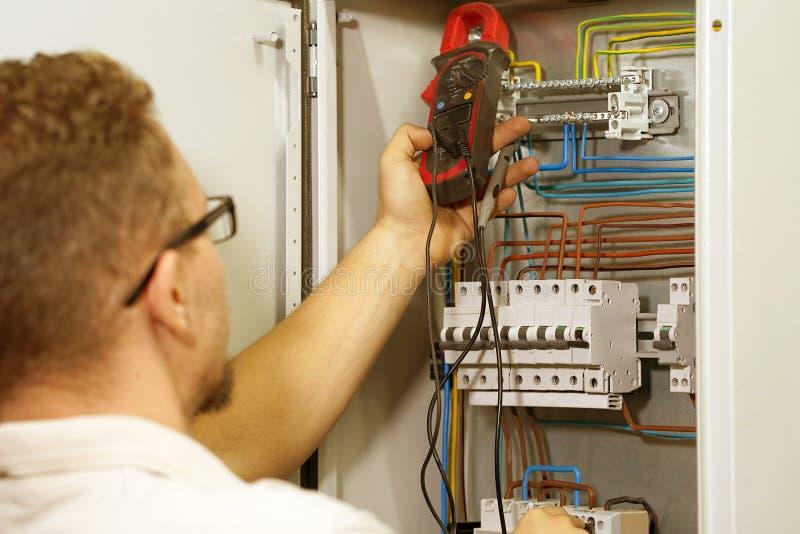 El multímetro está en manos del electricista en fondo del gabinete eléctrico de la automatización Ajuste del circuito de control  foto de archivo