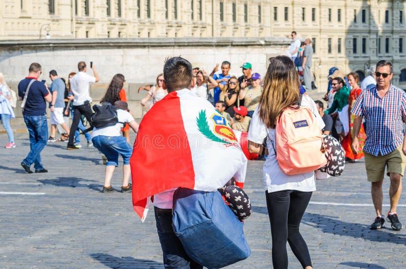 El mundial 2018 de la FIFA Fan peruana con la bandera de Perú en sus hombros en squar rojo imágenes de archivo libres de regalías