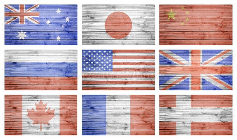 El mundo señala el collage por medio de una bandera sobre la textura de madera de los tablones fotografía de archivo libre de regalías