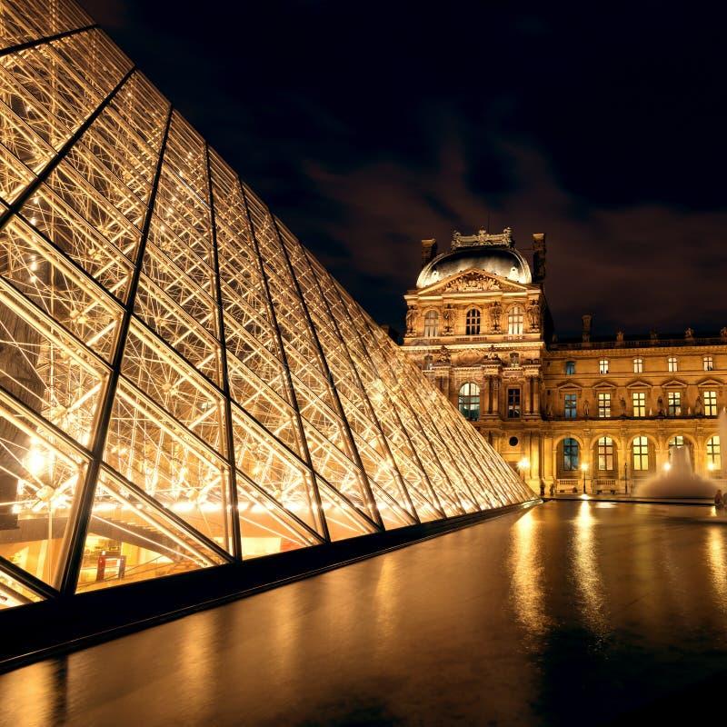 El museo del Louvre en la noche en París fotografía de archivo