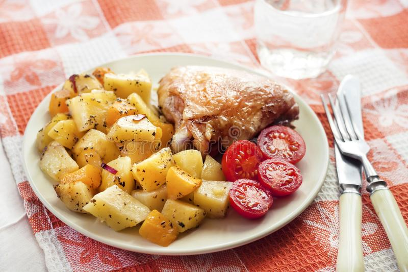 El muslo cocido del pollo con las patatas cocidas y la calabaza adornan foto de archivo