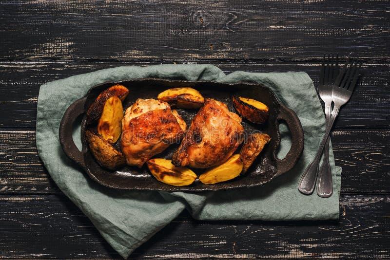 El muslo del pollo coció con las patatas en un plato negro Fondo rural, visión superior imagen de archivo