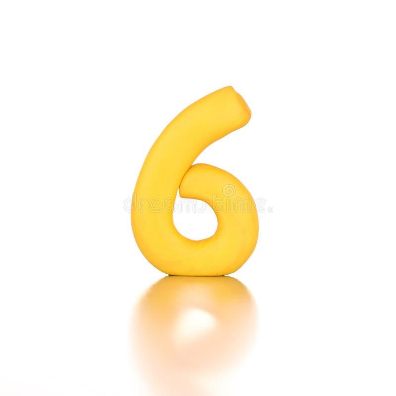 El número seis 6 hizo de amarillo aislado plasticine imagenes de archivo