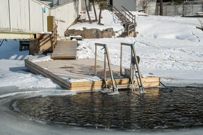 El nadar en agua helada usando una trayectoria de madera imagenes de archivo