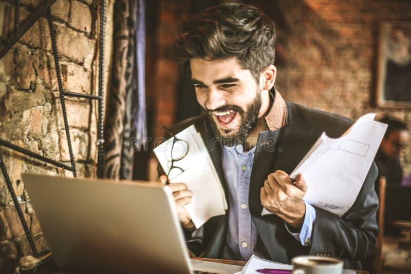 El negocio acertado hace que ríe Hombre de negocios joven fotos de archivo libres de regalías