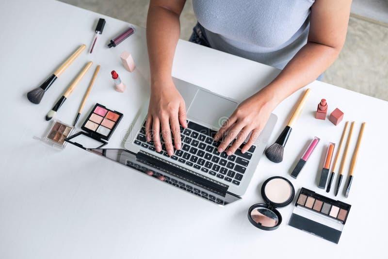 El negocio en línea en medios sociales, mujer hermosa está mirando tutorial en línea del blogger en el ordenador portátil, mostra fotografía de archivo libre de regalías
