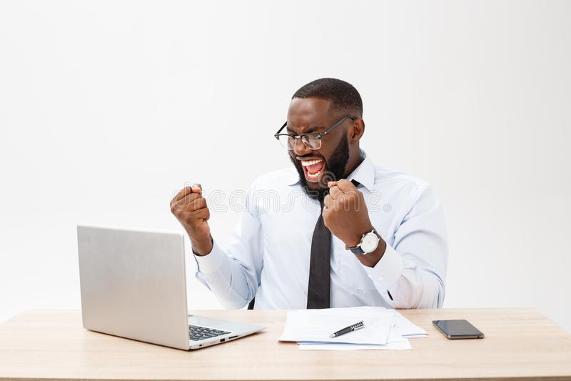 El negocio es su vida Hombre africano joven alegre en desgaste formal y trabajo en el ordenador portátil imágenes de archivo libres de regalías