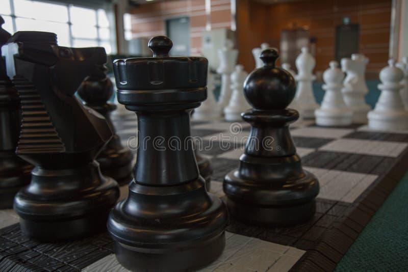 El negro del tablero de los pedazos de ajedrez junta las piezas de primero plano fotografía de archivo