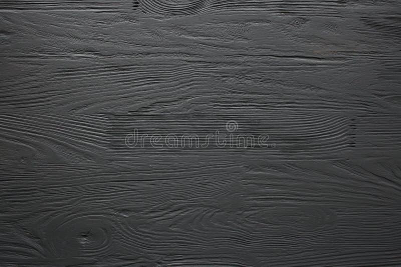 El negro pintó textura, el fondo y el papel pintado de madera foto de archivo