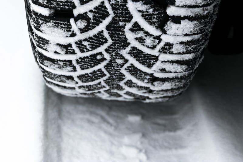 El neumático de coche en el cierre de la nieve para arriba Pistas del coche en la nieve Rastros del coche en la nieve Neumáticos  fotografía de archivo