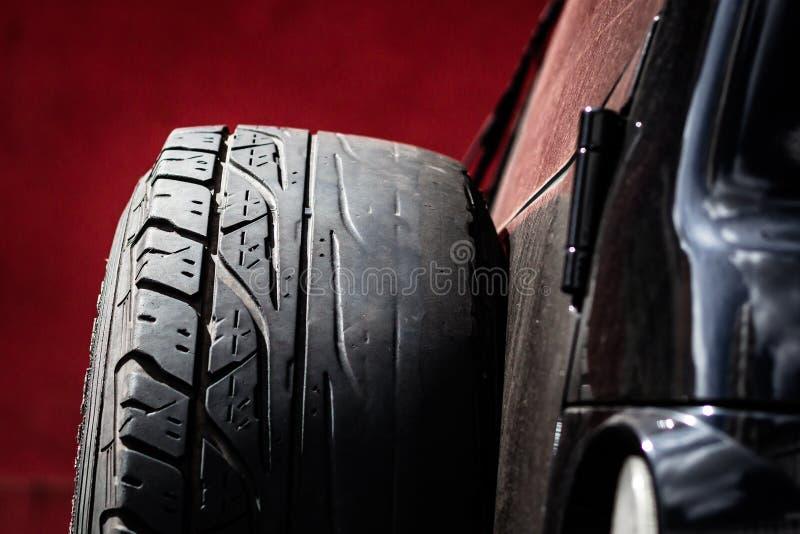 El neumático de repuesto con el Irregular utilizó el hilo bajo calvo imagen de archivo
