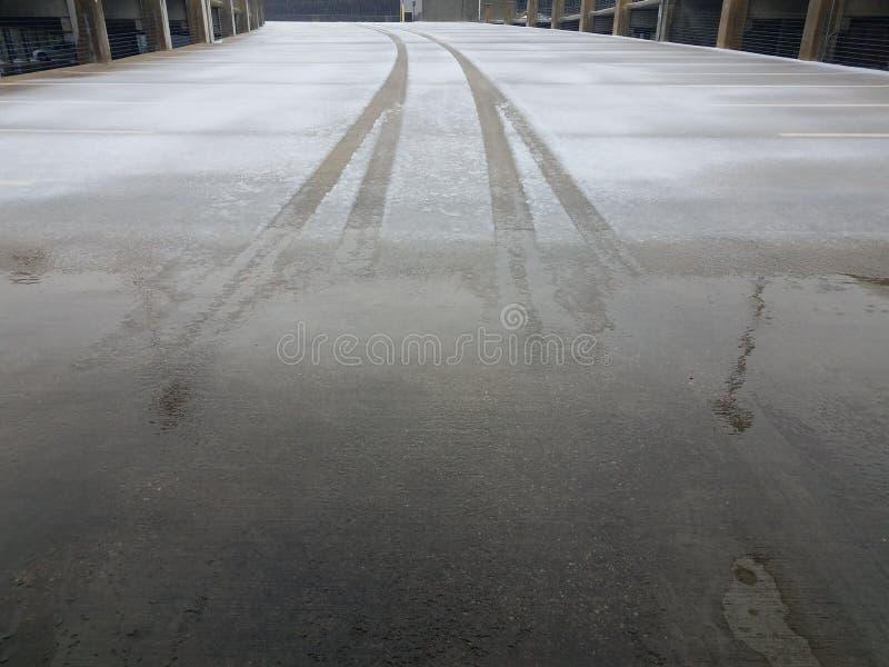El neumático sigue en el hielo y la nieve en la estructura que parquea imagen de archivo