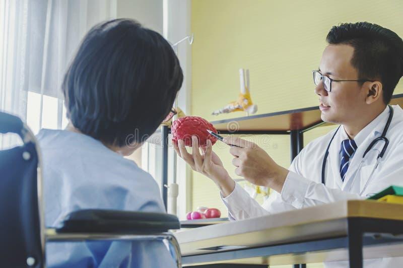 El neurólogo del doctor del hombre está mostrando a anciano el paciente femenino fotos de archivo
