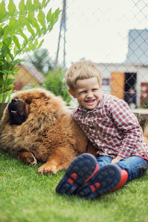 El niño abraza cariñosamente su perro casero Chow Chow imagen de archivo