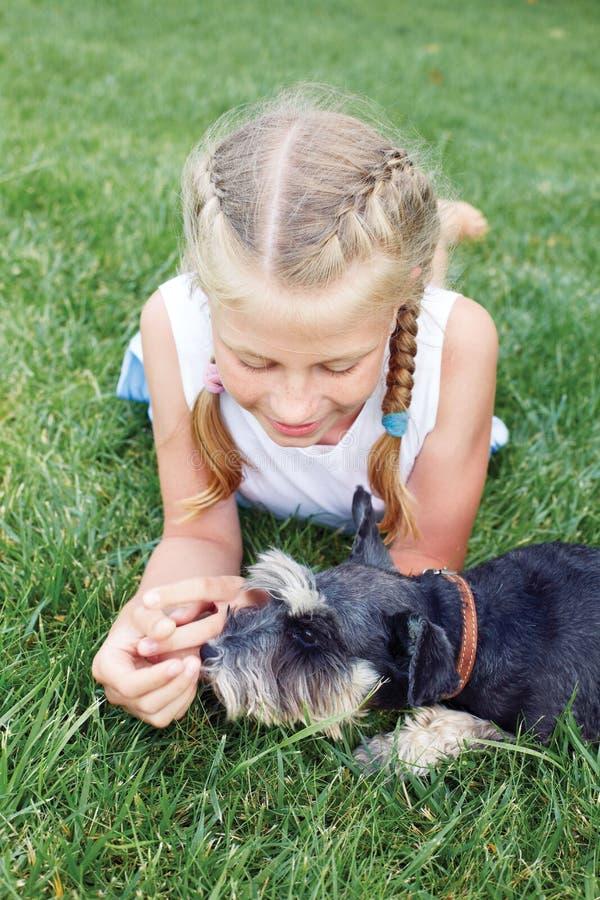 El niño abraza cariñosamente su perro casero, un schnauzer miniatura foto de archivo libre de regalías