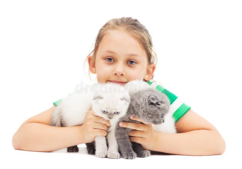 El niño abraza el gatito de orejas ca3idas británico tres fotografía de archivo