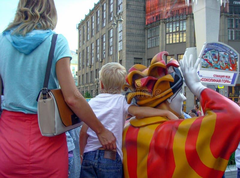 El niño abraza la escultura del payaso por el cuello foto de archivo