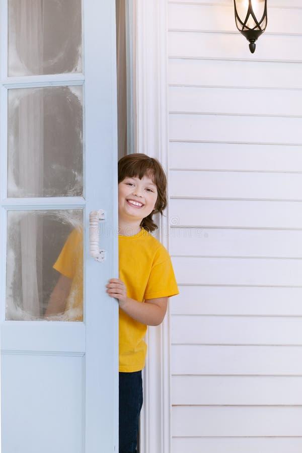 El niño abre la puerta de una casa imagen de archivo libre de regalías