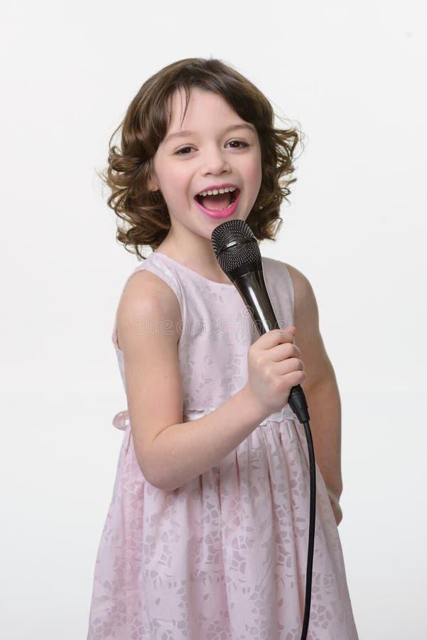 El niño adorable canta una canción fotos de archivo