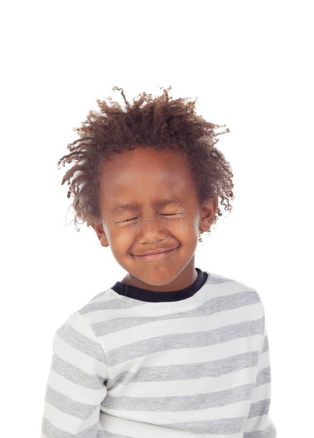 El niño africano que hace las caras divertidas que cierran el suyo observa fotos de archivo