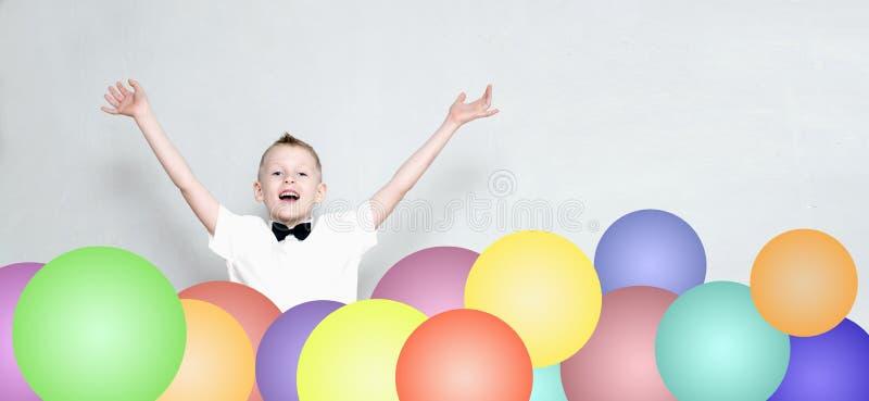 El niño alegre está saltando de los globos coloridos imagenes de archivo