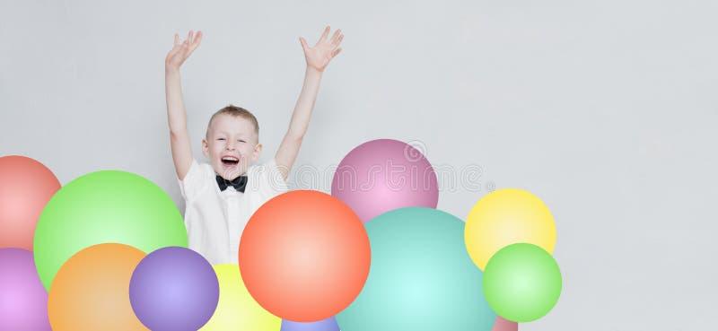 El niño alegre está saltando de los globos coloridos imagen de archivo