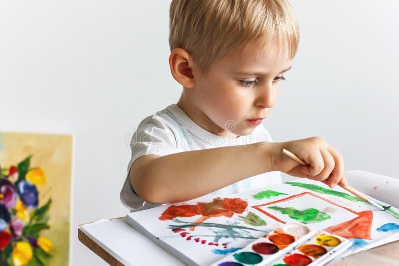 El niño alegre feliz dibuja las pinturas en un álbum, usando una variedad o imagen de archivo